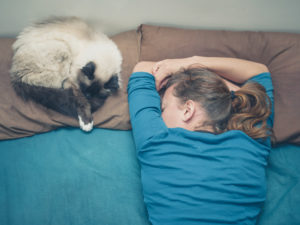 A young woman is sleeping in a bed with a cat next to her